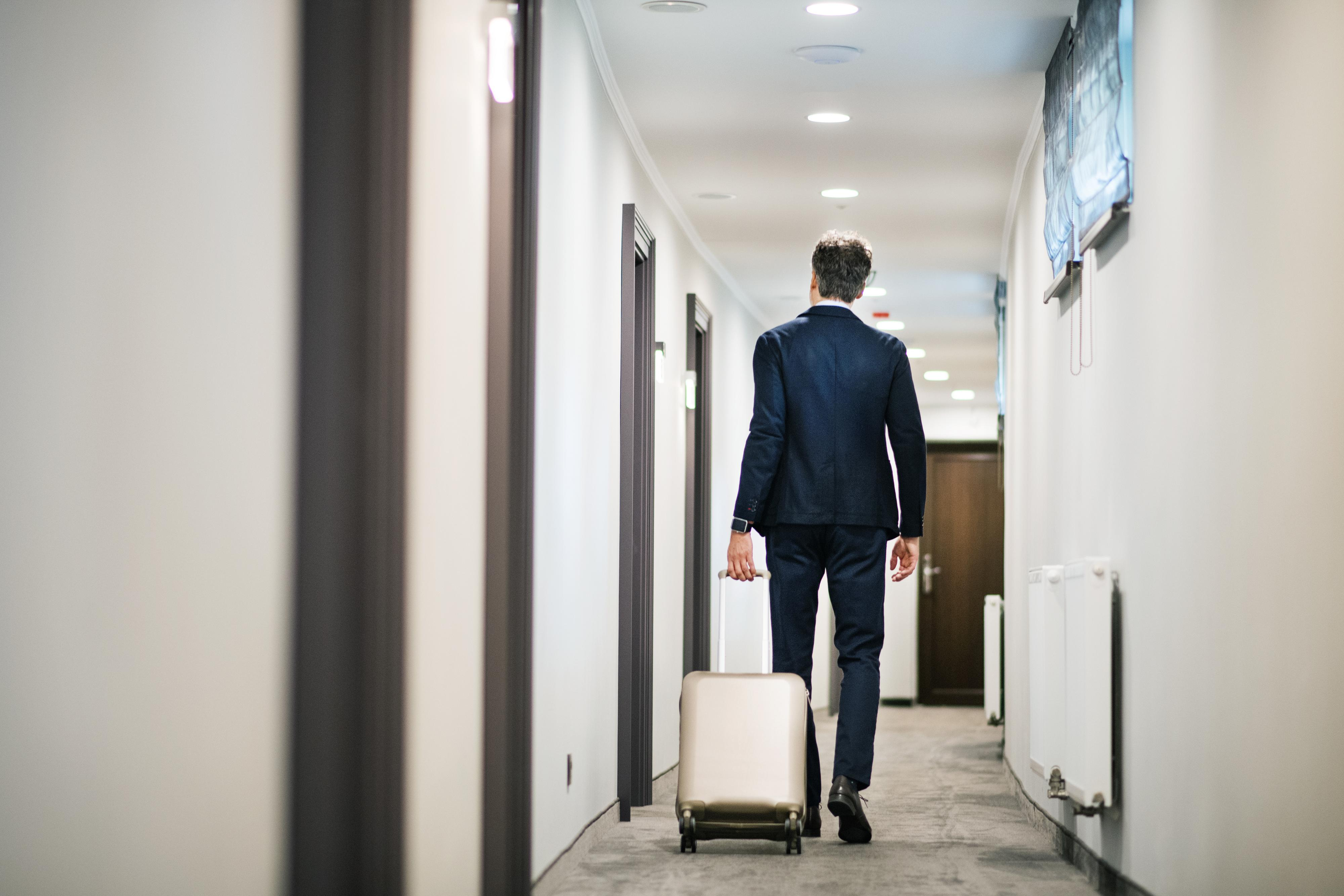 Businessman walking with luggage in a hotel corridor.
